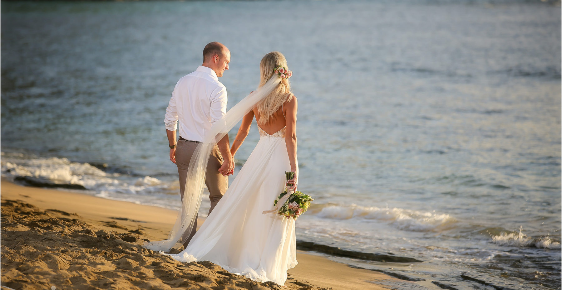 Newlywed couple hand in hand enjoying the ocean after their romantic beach elopement