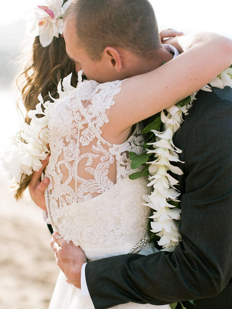 Couples embrace at their beach wedding on Kauai.