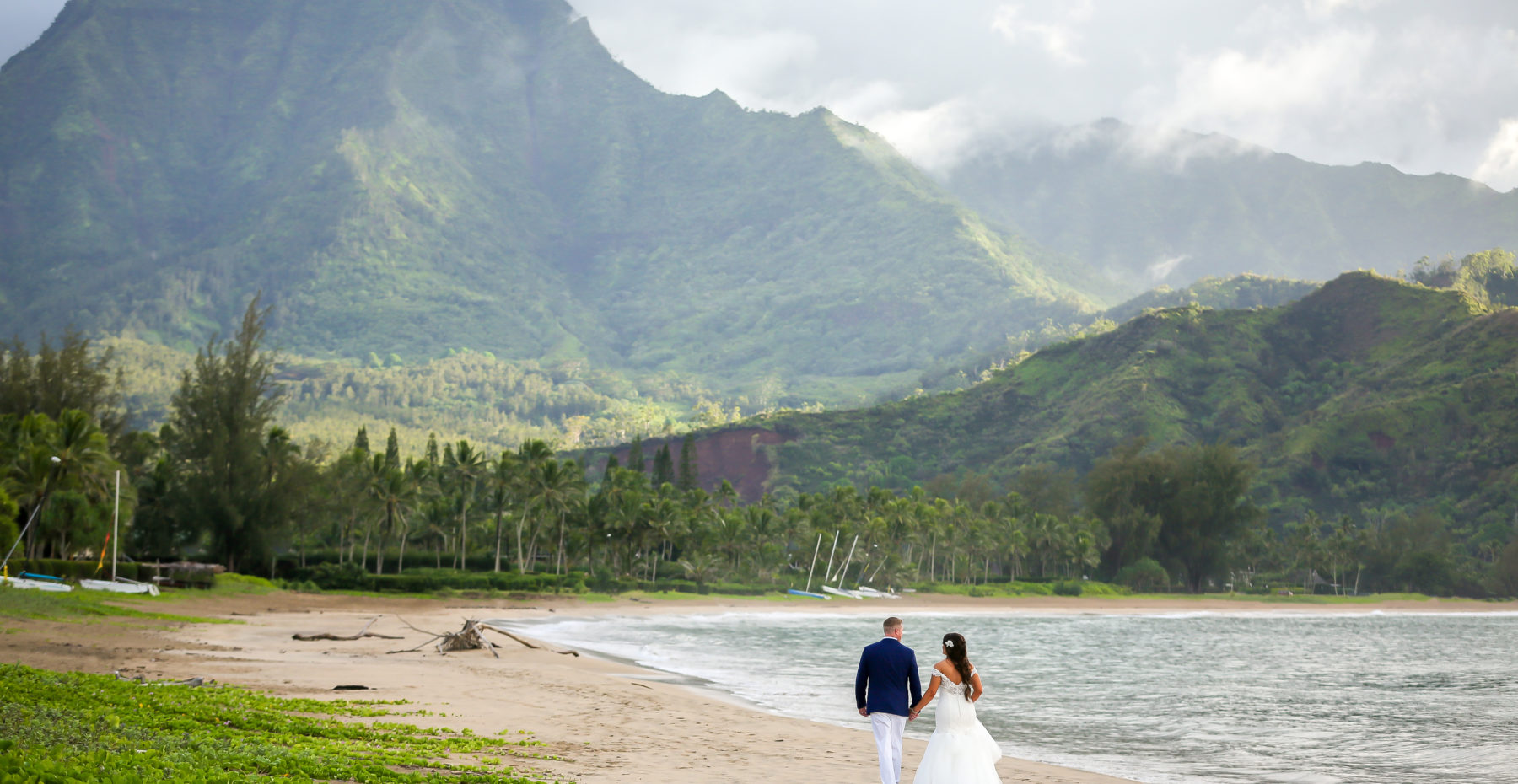 Bride and groom enjoy the beautiful mountain views at Hanalei Bay on Kauai.