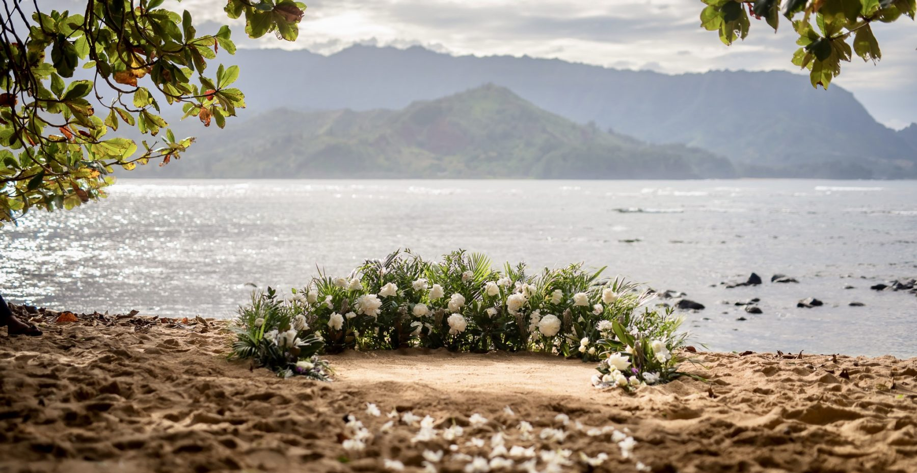 Lush green and white semi-circle of flowers for a beach elopement on Kauai