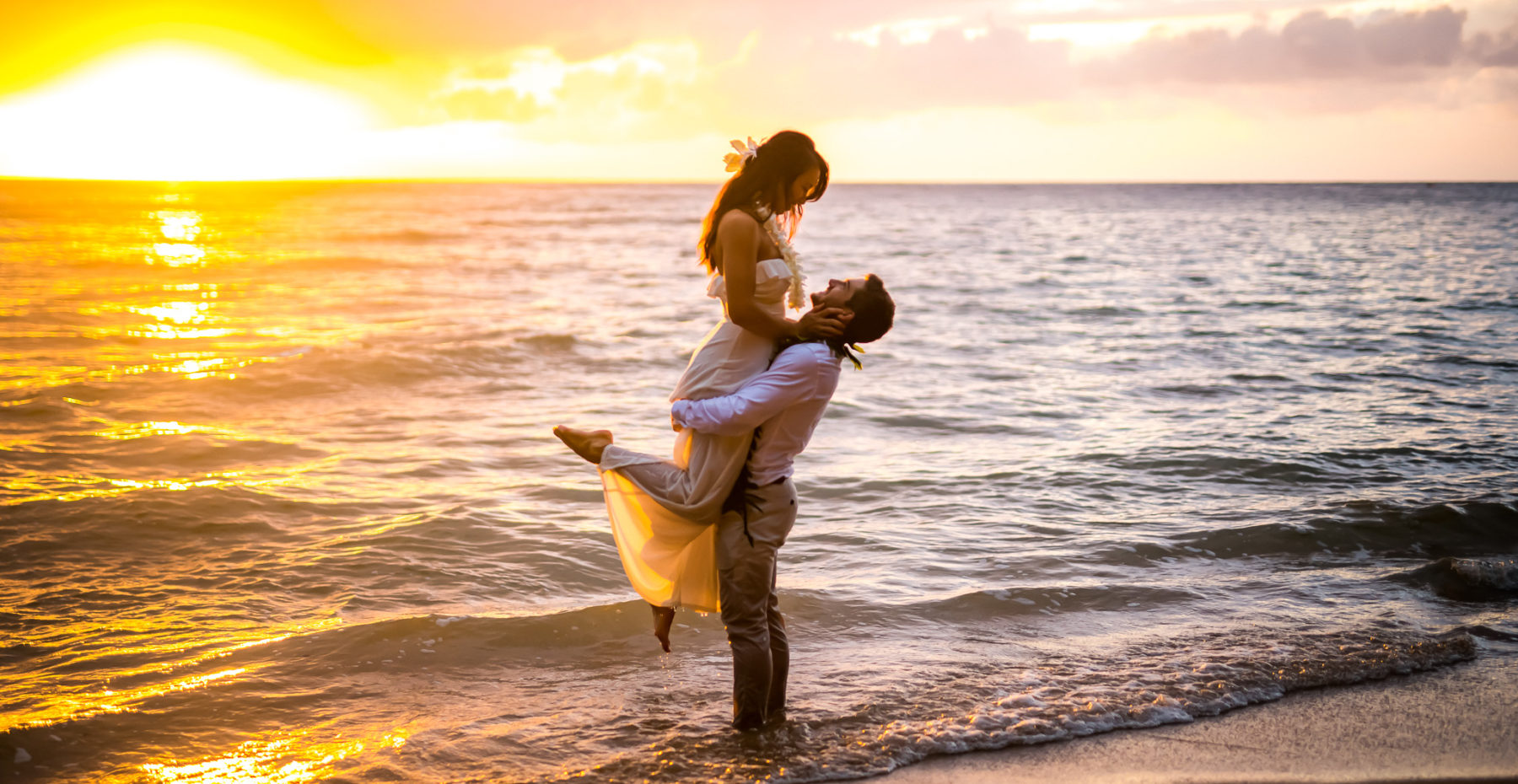 Groom holding bride in the ocean at sunset