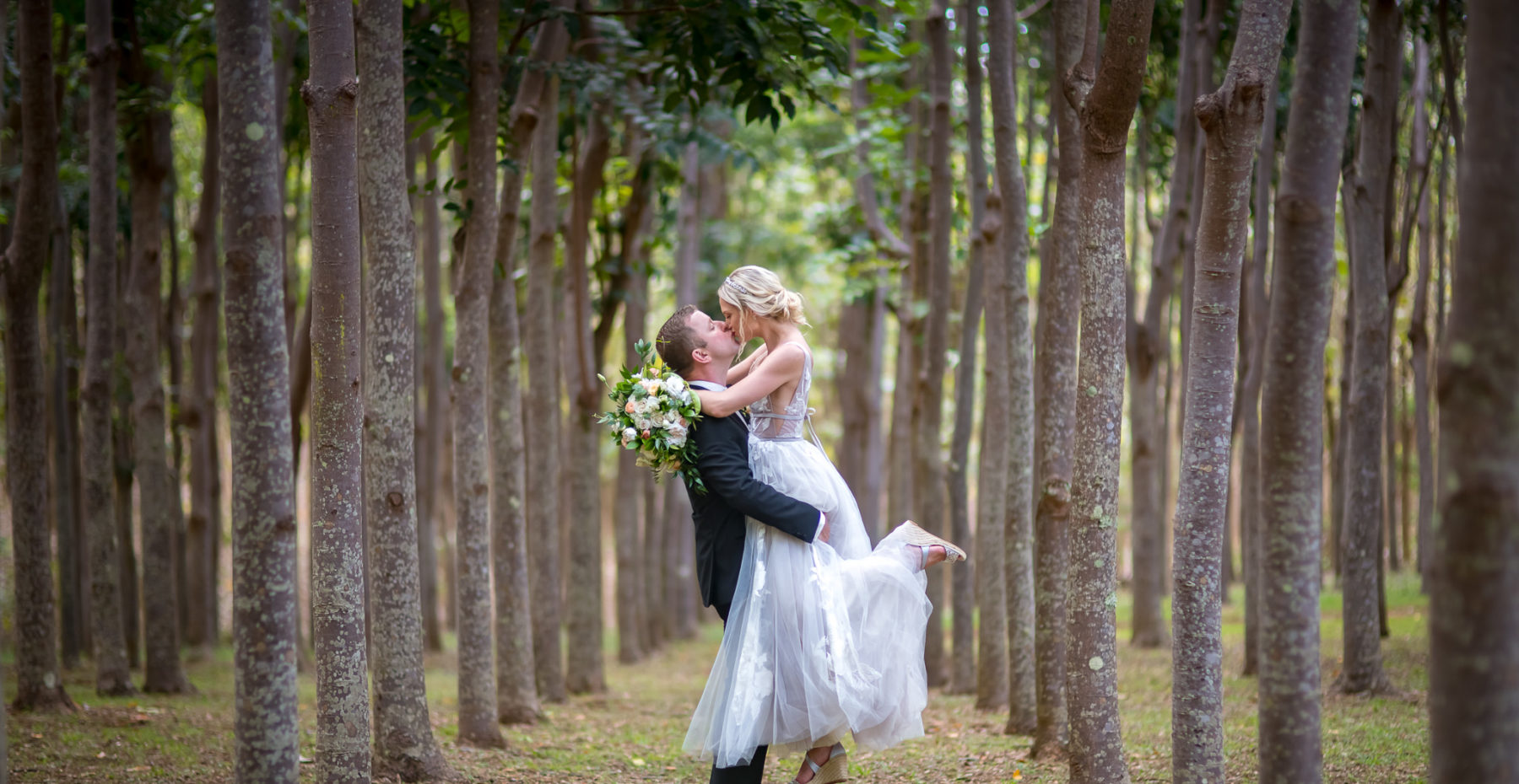 Newlyweds share their first kiss sealing their vows at a Botanical Garden wedding on Kauai.