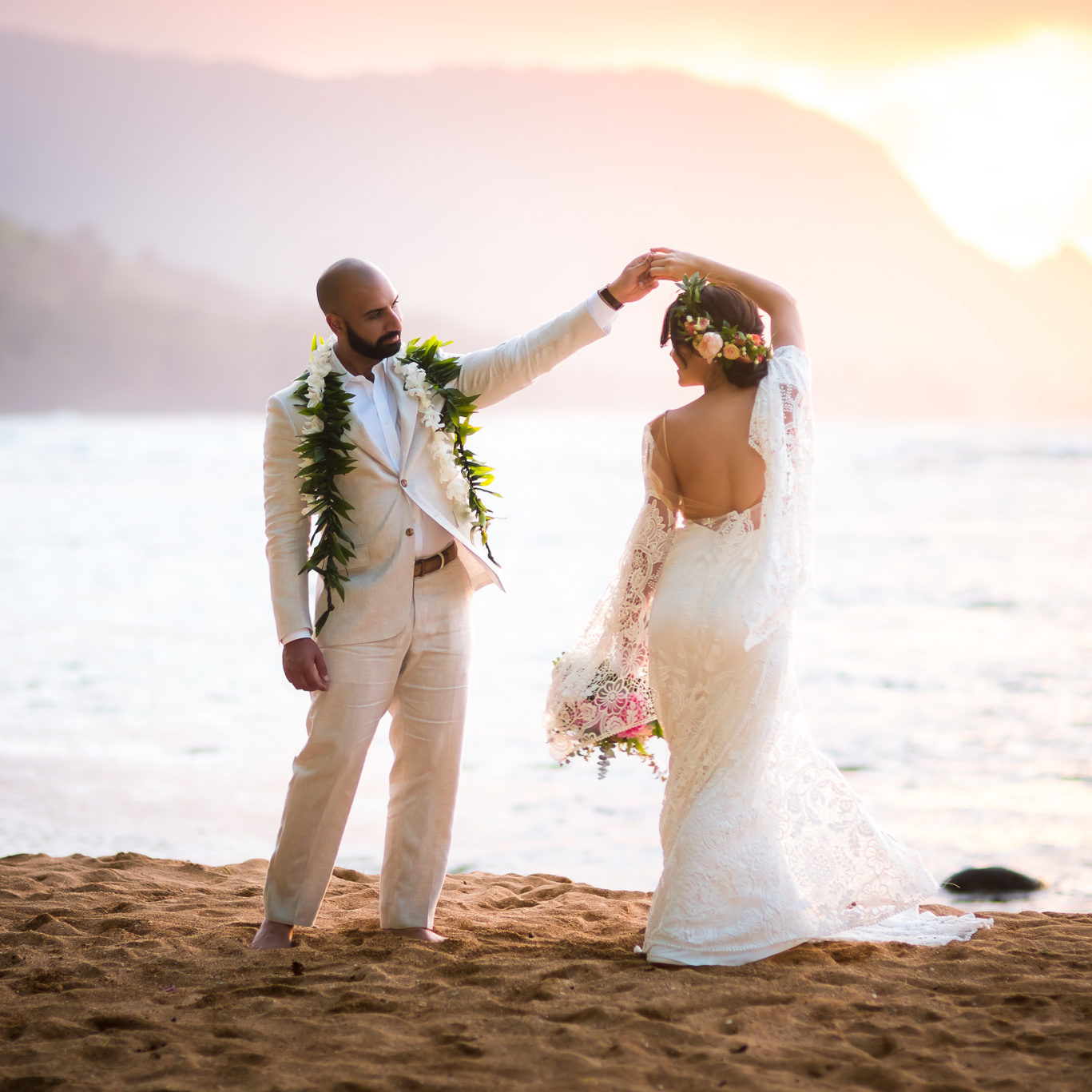 Bride and groom first dance on the beach as sunset