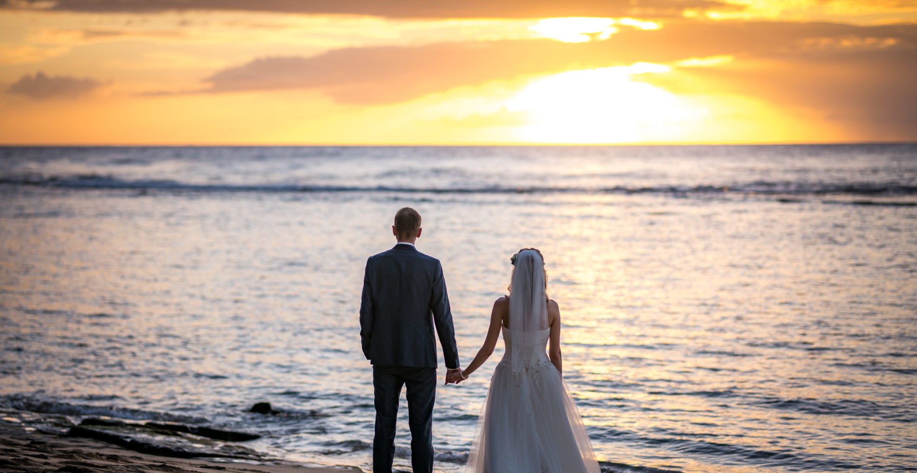 Romantic elopement with the groom awaiting his bride in a flower circle on a beautiful Kauai beach at sunset